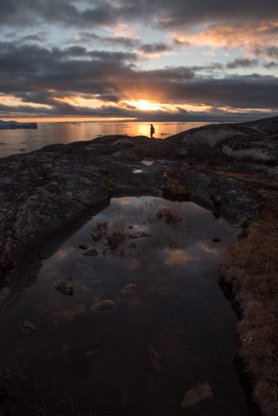 Sunset in Greenland. Golden light and a woman in front of the setting sun.