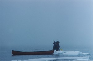 Two paddlers step off their canoe onto an ice flow