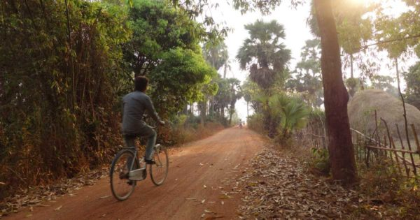 Man rides bike on dirt road