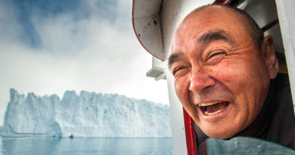 Man looking out window with iceberg