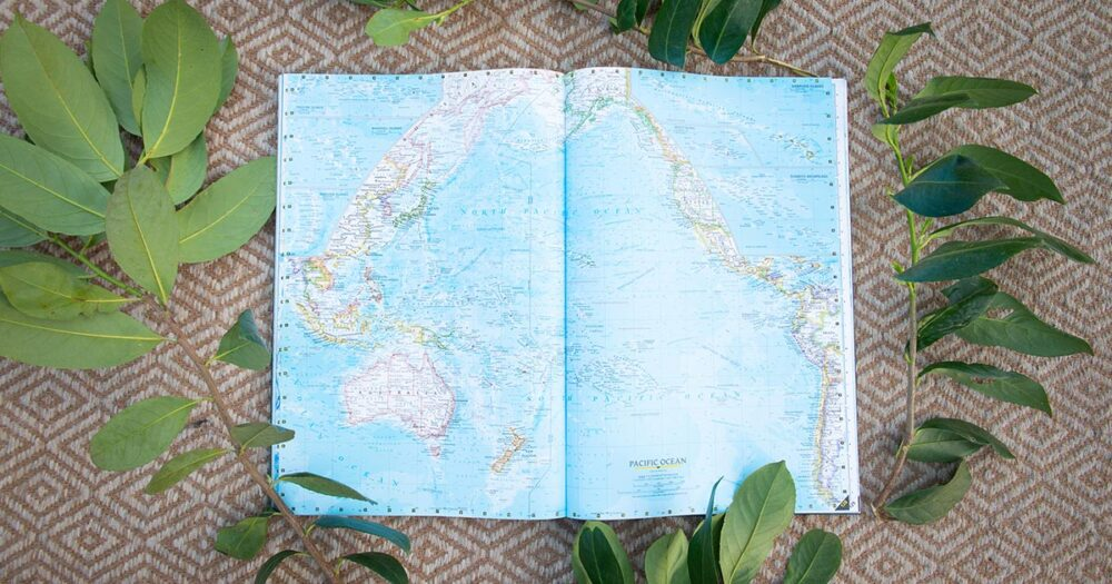 Map book of the world rests on the floor, open to the South Pacific pages.