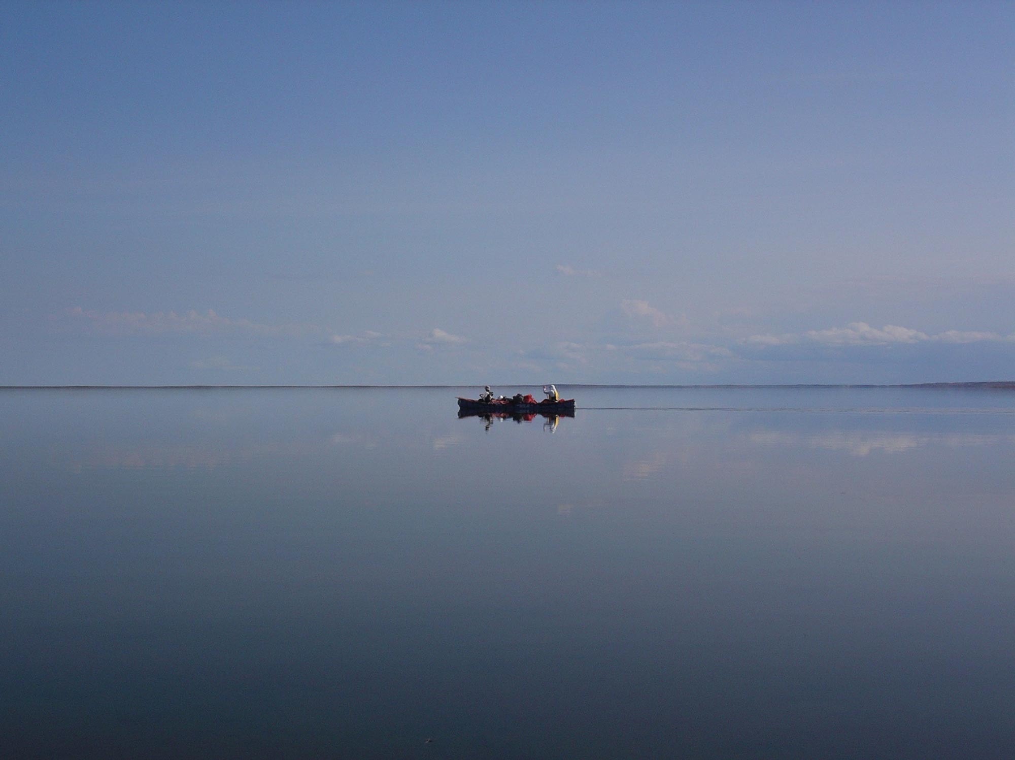 Two paddlers in a canoe on a giant mirror-still lake.