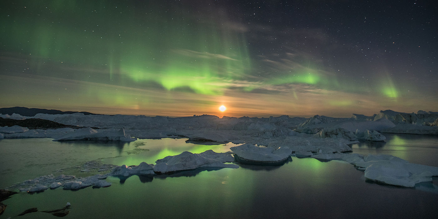A rising moon helps the northern lights to illuminate icebergs trapped within the Ilulissat Icefjord, a UNESCO World Heritage Site since 2004. The icebergs are calved from the Sermeq Kujalleq glacier located roughly 60 miles up fjord to the east. The town of Ilulissat lies 2 miles to the north of the Icefjord's mouth in western Greenland. September 2016
