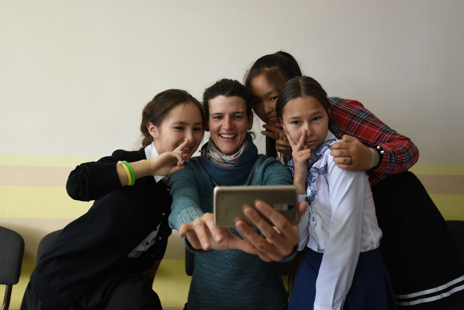 Jennifer Kingsley poses for a selfie with three young girls.
