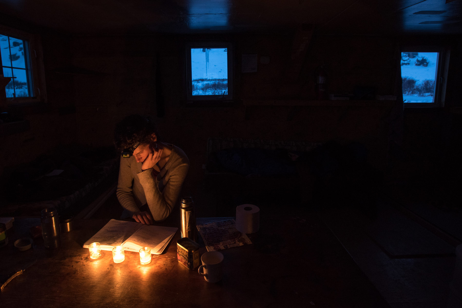 Jennifer Kingsley reads a map by candlelight in Alaska.