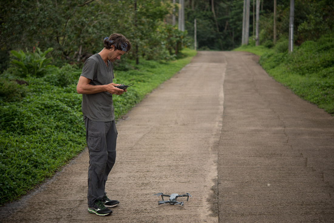 Man on dirt road with drone