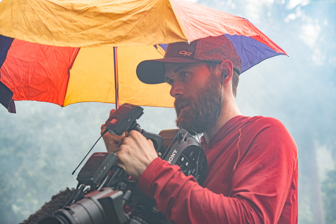 Cameraman shields his camera from rain with an umbrella.