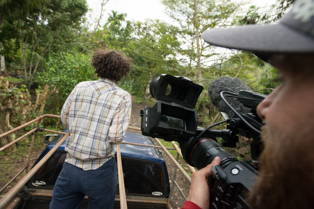 A cameraman films a woman as they both stand in the back of a truck that drives through a forest.