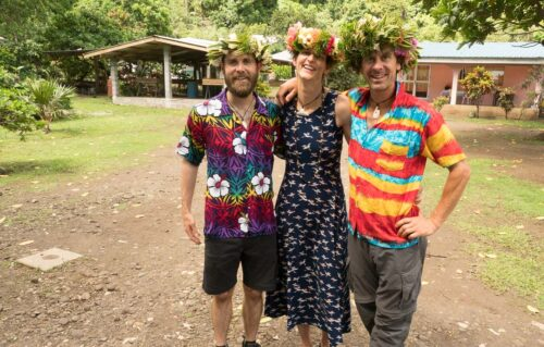 Two men and a woman with flower crowns smile at the camera