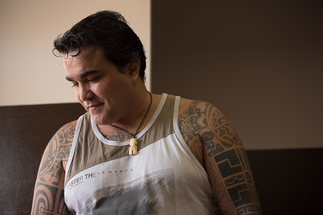Teiki, a man with traditional Marquesian tattoos on his arms, looks down at his work.