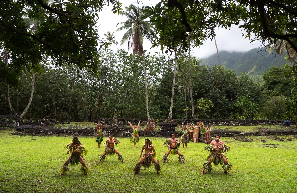 Local men and women perform a traditional dance in a field.