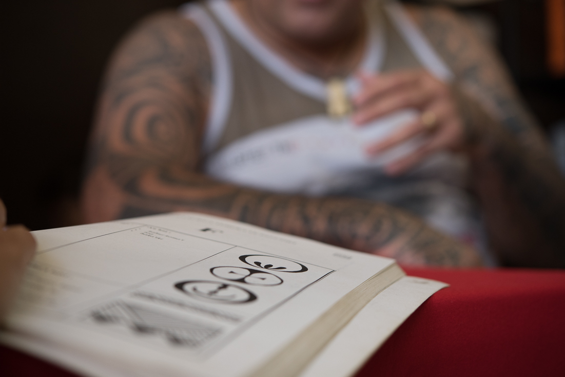 A tattoo artist sits behind his book of tattoo designs.