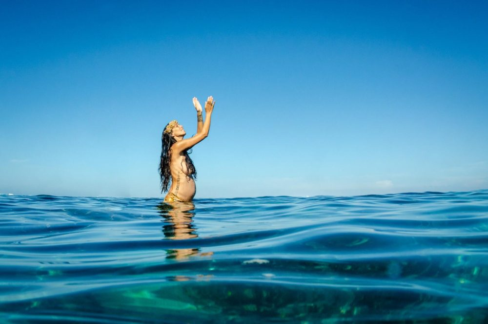 Woman stands to her waist in turquoise ocean water