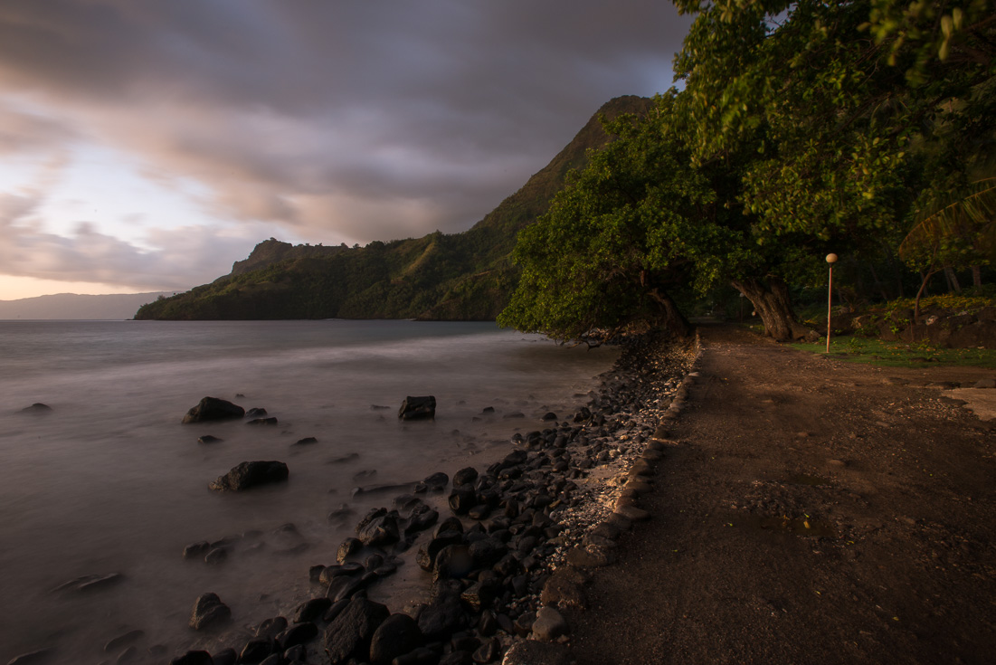 A rocky beach at sunset with mountains in the background.