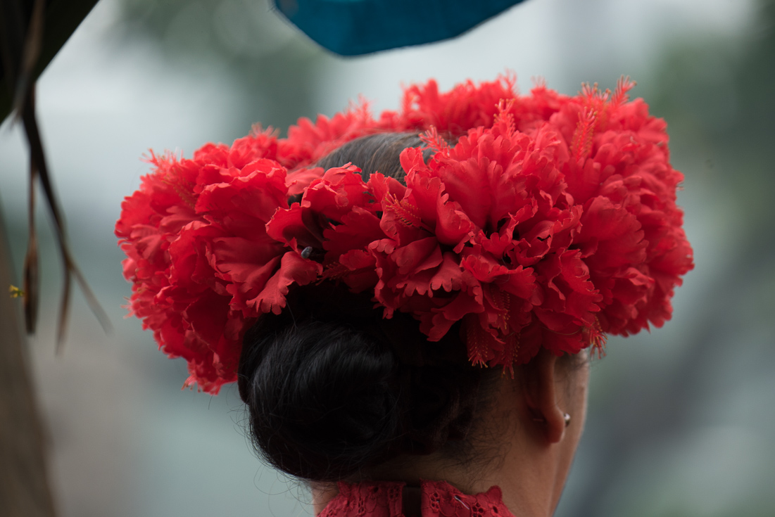 A woman wears a flower crown made up of red flowers.