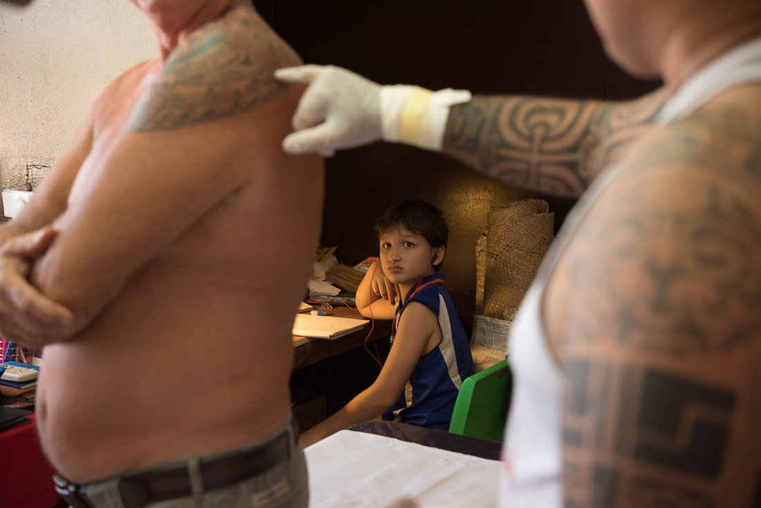 A tattoo artist points to the traditional tattoo on his client's shoulder while a child looks on.