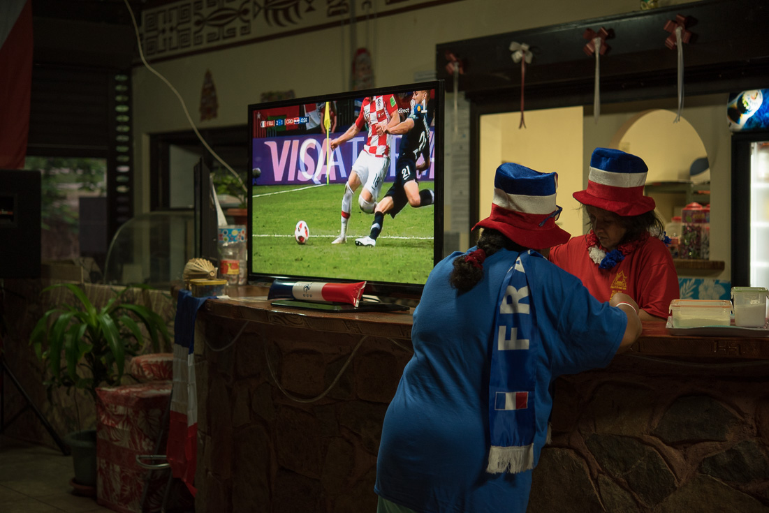 A woman watches a world cup game from the inside of a bar while the bartender makes drinks.