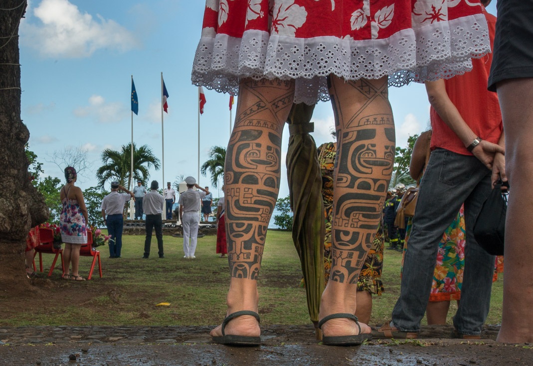A woman's legs are covered in traditional Marquesian tattoos.
