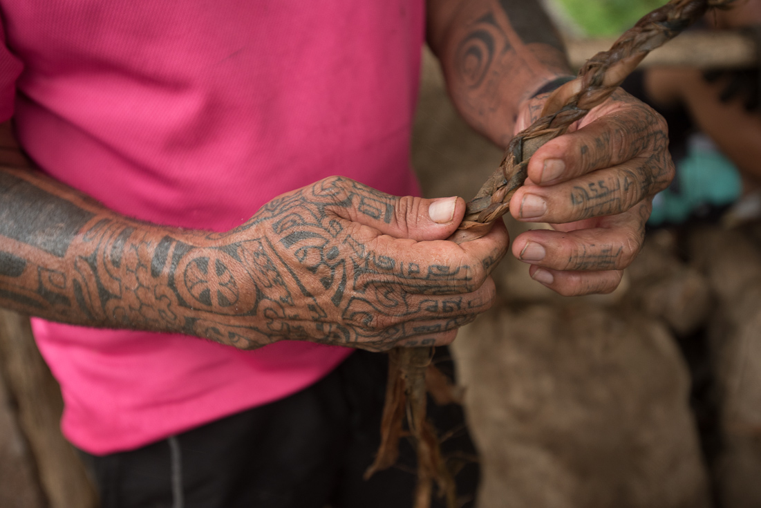 A man's hands and arms are covered in traditional tattoos.