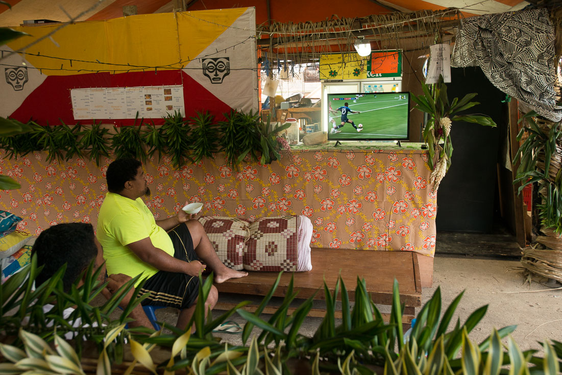 Two men watch a World Cup match from a restaurant patio