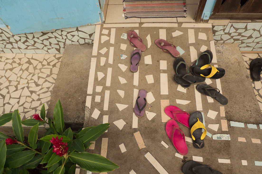 Multiple pairs of flip flop sandals are placed outside the entrance of a home.