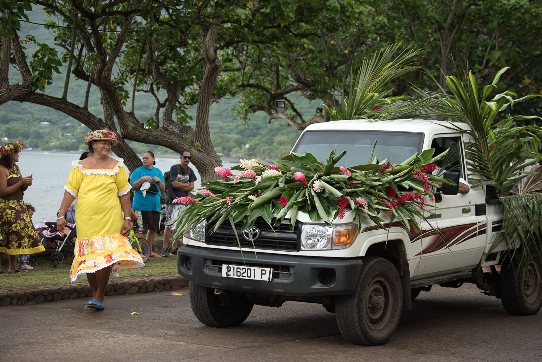 A woman in a yellow dress walks by a truck that is covered in local flowers.