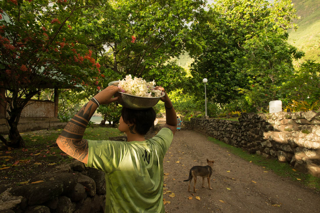 A man with traditional tattoos carries food in a bowl on top of his head while a dog stands near him.