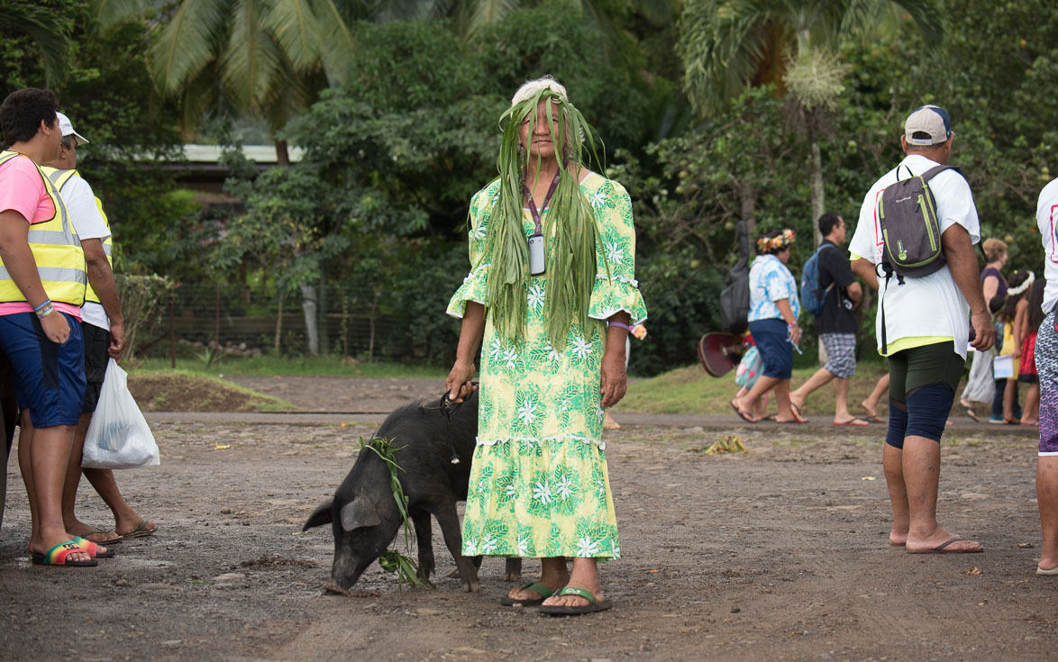 A woman stands by a pig, and wears local plants in her hair.