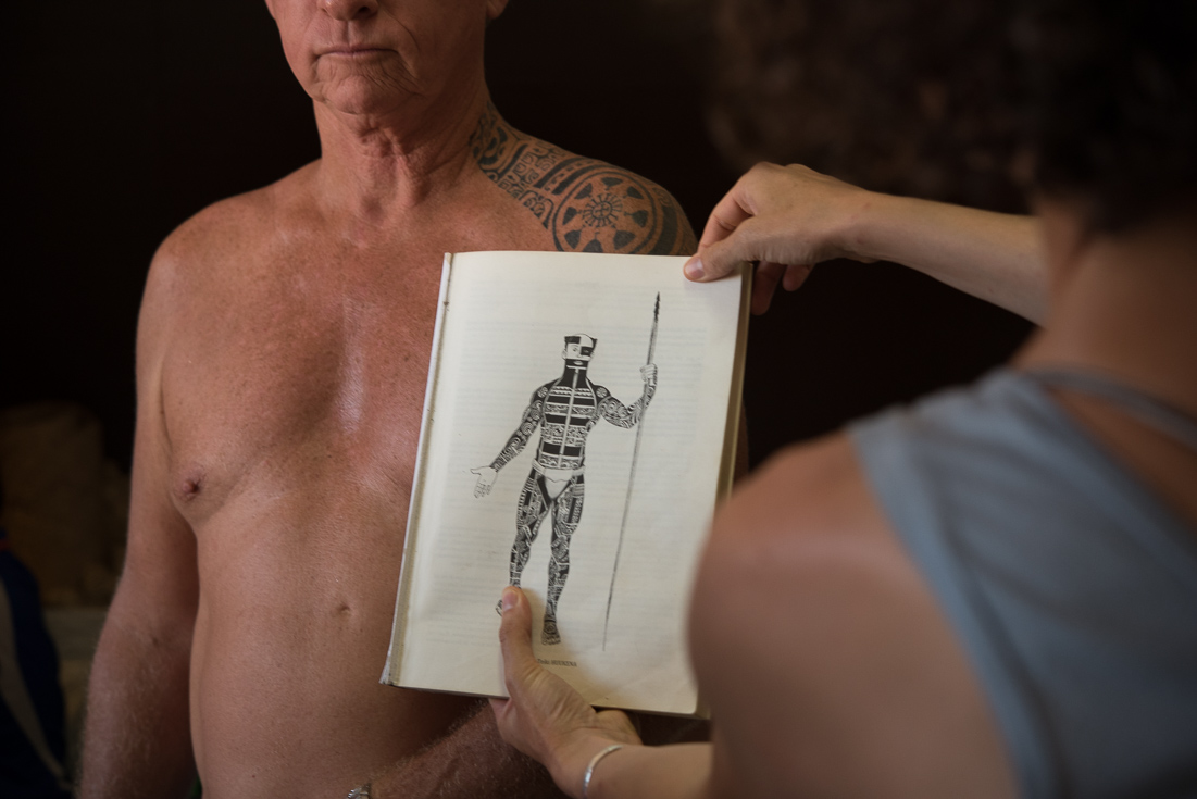 A man stands shirtless as a woman holds up a historical sketch of a man covered in traditional tattoos.