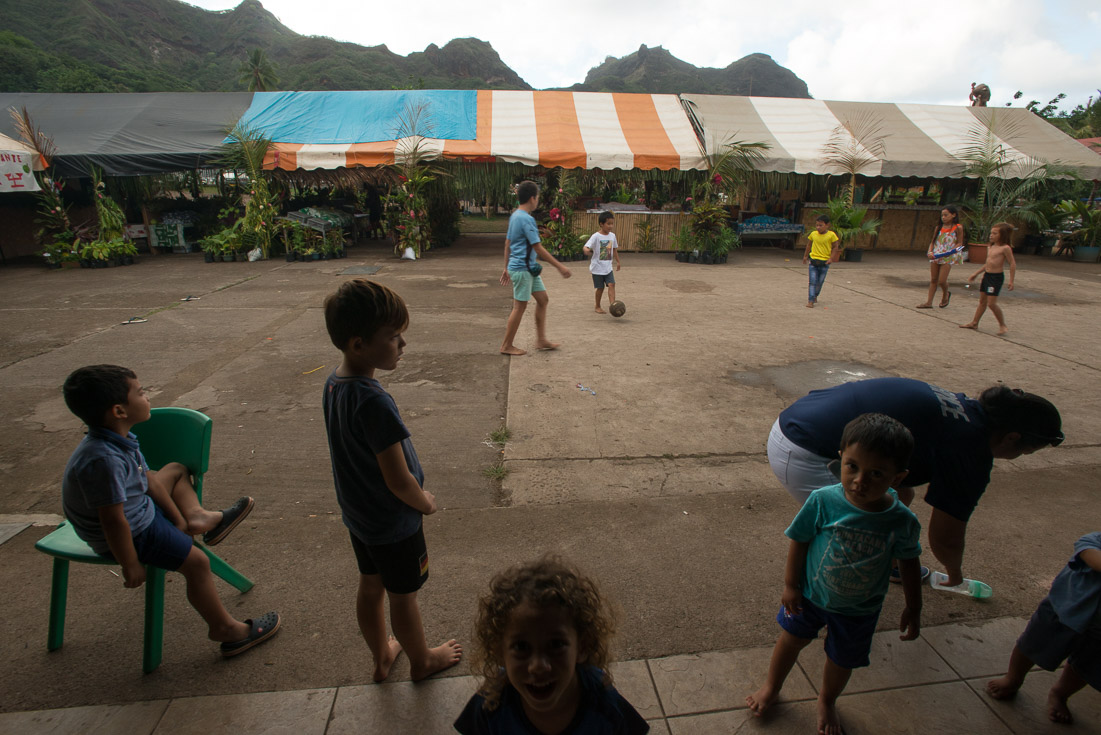 Local children play soccer outside while other children watch.