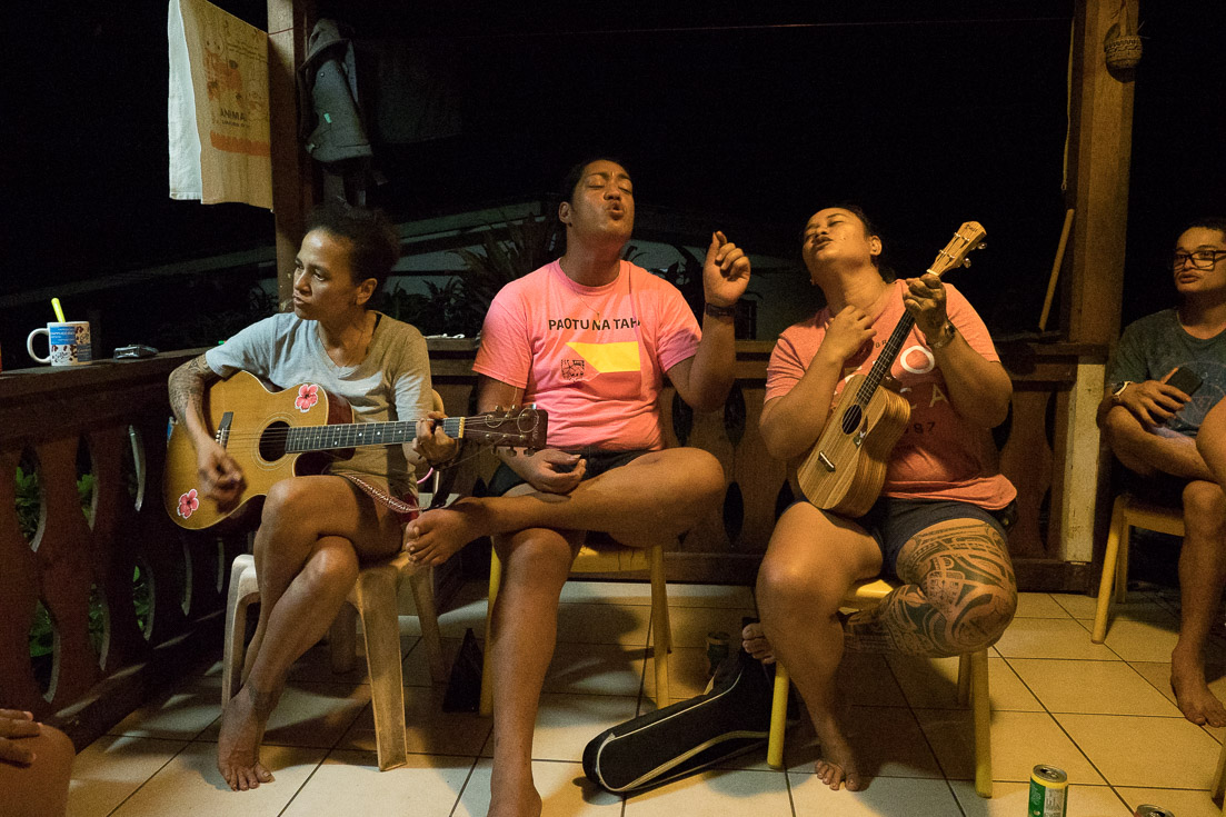 A local family plays guitar, ukulele and sings in the inside of their home.