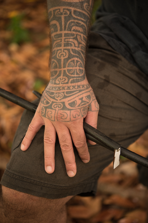 A heavily tattooed arm and hand up close.
