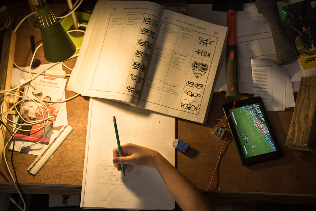 A child practices drawing traditional tattoos while a world cup plays on an iPhone screen next to his sketchbook.