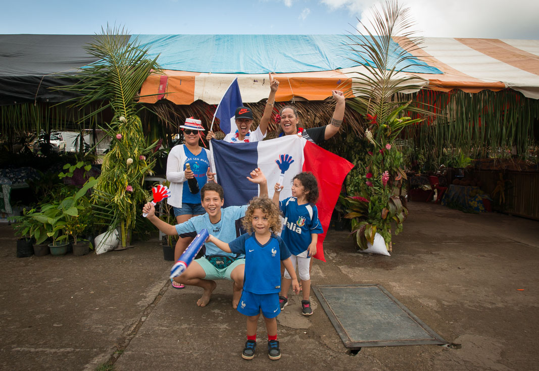 A family holds up a French flag and cheers.