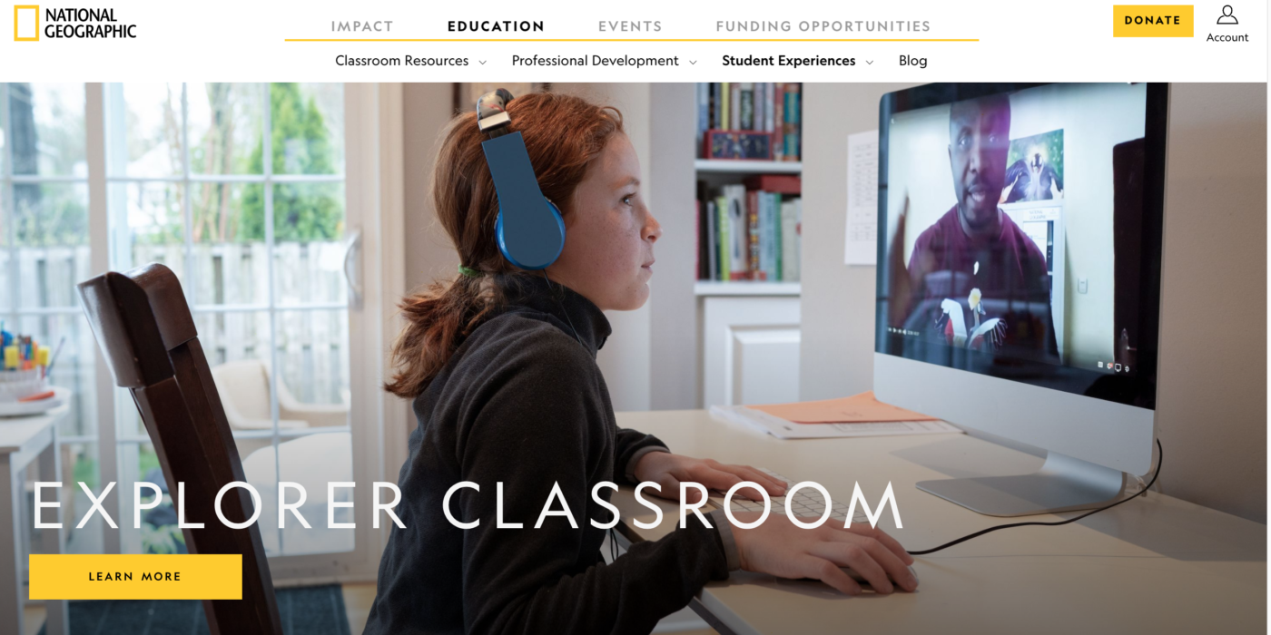 Young girl with headphones looks at computer screen