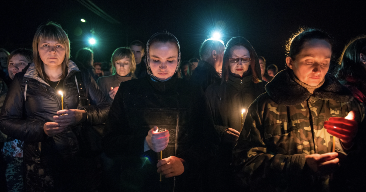 Women stand together in the night and hold candles